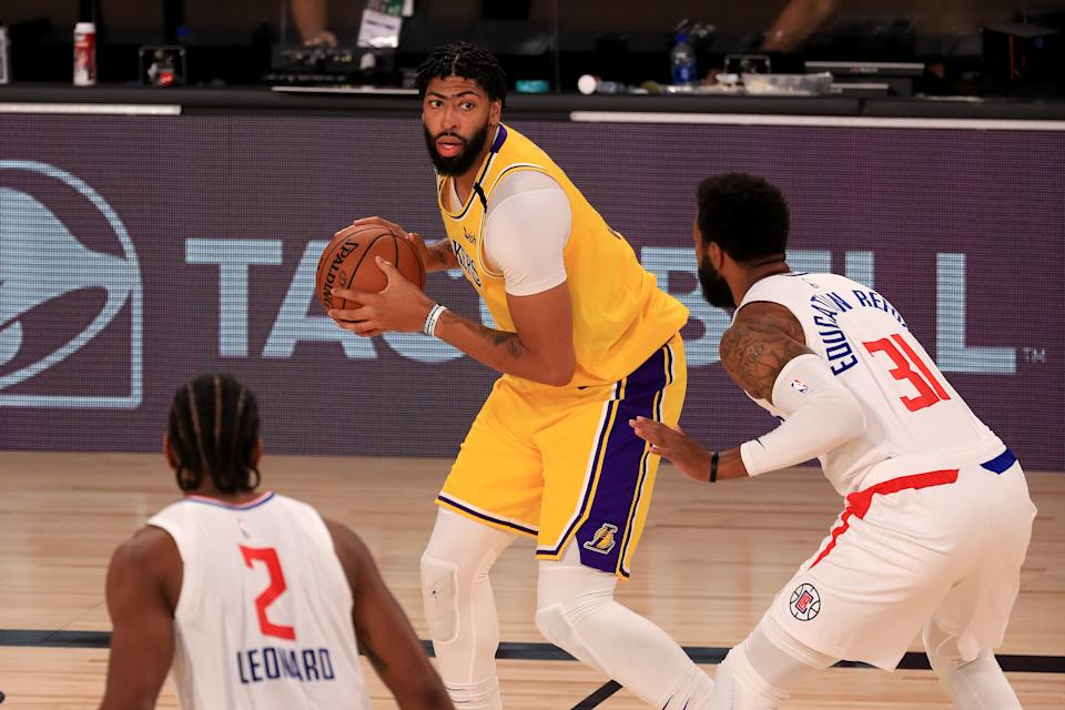 LAKE BUENA VISTA, FLORIDA - JULY 30: Anthony Davis #3 of the Los Angeles Lakers looks to pass against Marcus Morris Sr. #31 of the LA Clippers during the third quarter of the game at The Arena at ESPN Wide World Of Sports Complex on July 30, 2020 in Lake Buena Vista, Florida. NOTE TO USER: User expressly acknowledges and agrees that, by downloading and or using this photograph, User is consenting to the terms and conditions of the Getty Images License Agreement. (Photo by Mike Ehrmann/Getty Images)