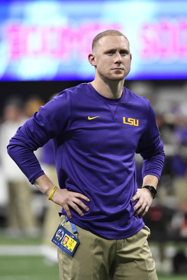 LSU offensive coach Joe Brady watches his team warm up before the first half of the Peach Bowl NCAA semifinal college football playoff game between LSU and Oklahoma, Saturday, Dec. 28, 2019, in Atlanta. (AP Photo/Danny Karnik)