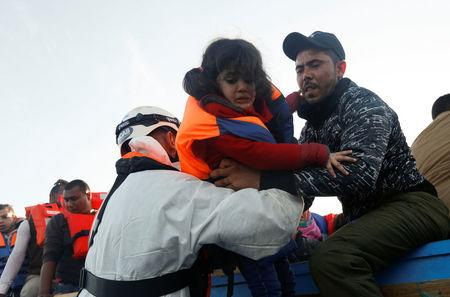 Rescuers of the Malta-based NGO Migrant Offshore Aid Station (MOAS) rescue a child migrant from a wooden boat in the central Mediterranean