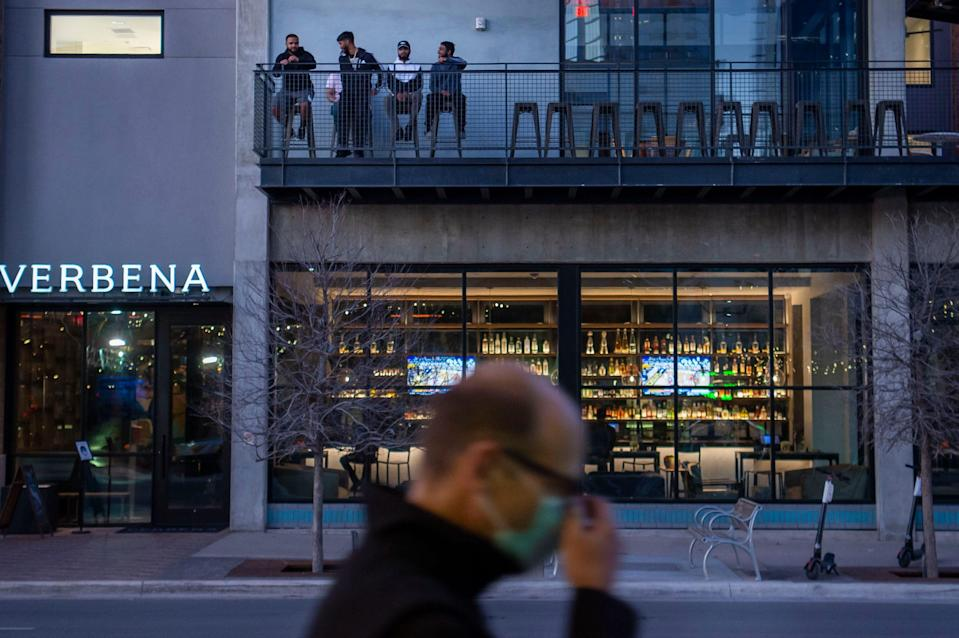 People drink on the upper level of Verbena on  March 2 in Austin, Texas. Texas Gov. Greg Abbott rescinded the statewide mask mandate, allowing businesses to open at 100% capacity next week.