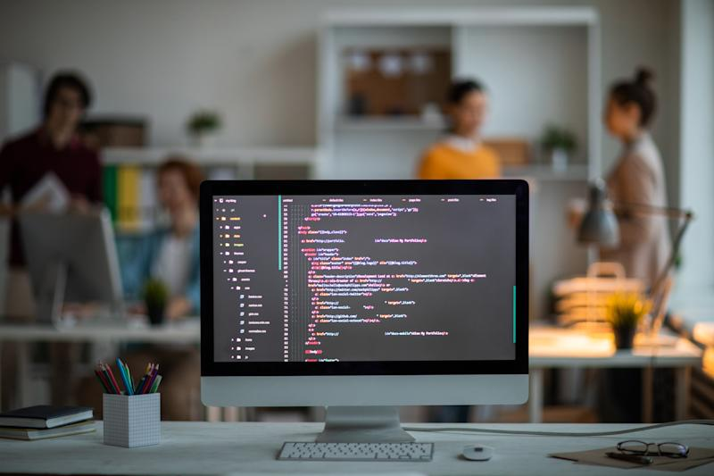 Workplace of it-developer or programmer with computer screen with coded data on background of office workers