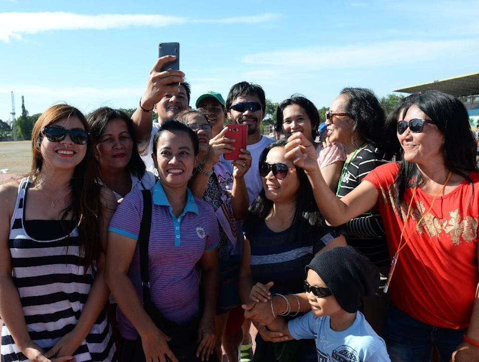 A defiant Manny Pacquiao (C) poses for photos with visitors at a Philippine sports complex after making gay slurs that have tarnished his reputation and cost him millions in endorsements (AFP Photo/Ted Alibe)