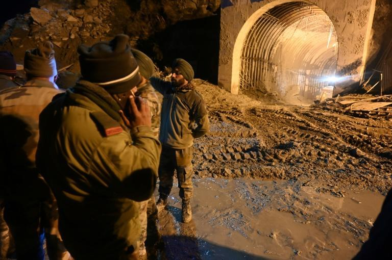 Indian army and rescue teams stand outside the entrance of a tunnel blocked with mud and debris during rescue operations following a deadly flash flood in northern India