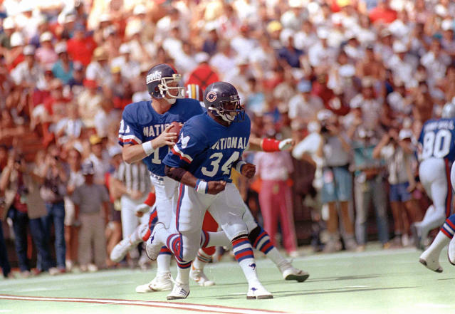 File-This 1986, file photo shows New York Giants quarterback Phil Simms (11) dropping back to pass while the Chicago Bears running back Walter Payton (34) gets set to block him during Pro Bowl Games in Hawaii. TV ratings for the Pro Bowl lag below all the prime time regular season games, and the on-field intensity and drama that fuels so much of the national interest in the sport is nonexistent. The annual all-star exhibition does not lack for history, however, with a genesis traced back to the 1938 season. (AP Photo/File)