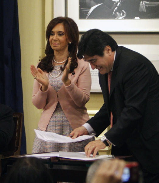 FILE - In this July 21, 2010 file photo, Argentina's President Cristina Fernandez, left, applauds after signing the same sex marriage bill at the government house accompanied by presidential legal aid Carlos Zannini, in Buenos Aires, Argentina. An Argentine judge on Thursday, Dec. 7, 2017, accused Fernandez of the crime of treason as he asked lawmakers to remove Fernandez's immunity from prosecution as a senator. The judge has also ordered the arrest of Zannini. (AP Photo/ Eduardo Di Baia, File)