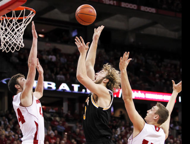 Milwaukee's Kyle Kelm, center, shoots between Wisconsin's Frank Kaminsky, left, and Sam Dekker during the first half of an NCAA college basketball game on Wednesday, Dec. 11, 2013, in Madison, Wis. (AP Photo/Andy Manis)