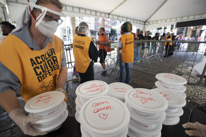 """Volunteers from a Christian church serve food to homeless people, in containers covered with the Portuguese message: """"With love,"""" during a quarantine imposed by the state government to help contain the spread of the new coronavirus in Sao Paulo, Brazil, Monday, April 27, 2020. (AP Photo/Andre Penner)"""