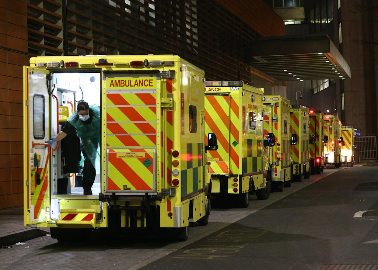 A paramedic opening the rear door of one of the ambulances queued outside the Royal London Hospital, in London.