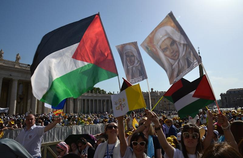 Pilgrims wave Palestinian flags before a holy mass in St Peter's Square for the canonization of four nuns, at the Vatican on May 17, 2015 (AFP Photo/Alberto Pizzoli)