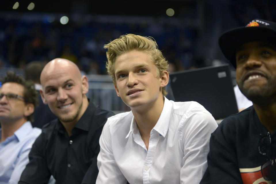 """Singer Cody Simpson, second from right, watches an Orlando Magic game from his court-side seats during the first half of an NBA basketball game against the Toronto Raptors in Orlando, Fla., Thursday, Jan. 24, 2013. Simpson was dominating attention ahead of Australia's Olympic swimming trials, until Maddie Groves pulled out of the six-day meet following a series of social media posts condemning """"misogynistic perverts"""" in the sport.(AP Photo/Phelan M. Ebenhack)"""