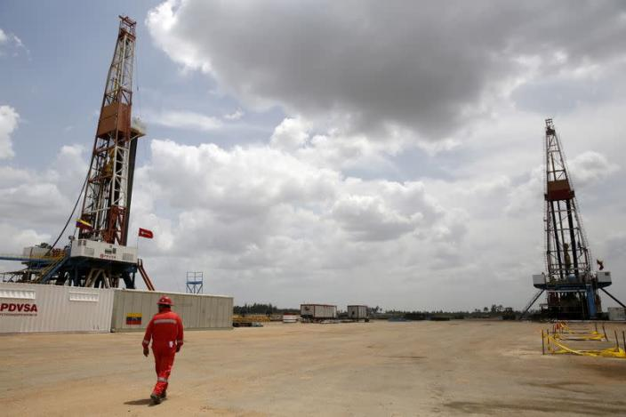 FILE PHOTO: An oilfield worker walks next to drilling rigs at an oil well operated by Venezuela's state oil company PDVSA