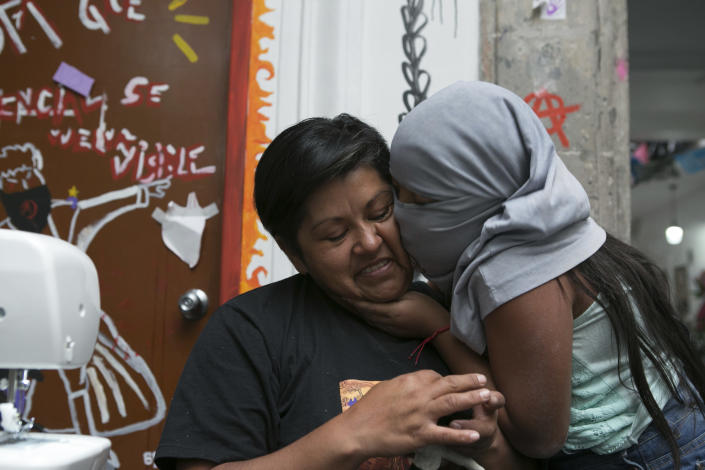 Erika Martinez gets a kiss from her 10-year-old daughter, who hides her identity with a T-shirt, as she makes key chains to sell while living inside Mexico's Human Rights Commission (CNDH) headquarters, which has been converted into a refuge for victims of gender violence like Martinez and her daughter, after women's rights activists occupied it three months ago in Mexico City, Tuesday, Nov. 17, 2020. Martinez said she was sexually abused when she was 10-years-old but the attack was never reported by her parents, and that her daughter suffered the same fate from her brother-in-law three years ago when she was just 7, and that her attacker remains free despite her reporting it to authorities. (AP Photo/Ginnette Riquelme)