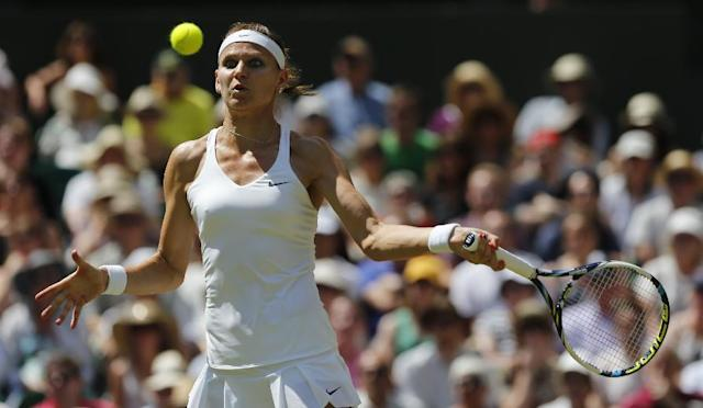 Lucie Safarova of Czech Republic plays a return to Petra Kvitova of Czech Republic during their women's singles semifinal match at the All England Lawn Tennis Championships in Wimbledon, London, Thursday, July 3, 2014. (AP Photo/Ben Curtis)