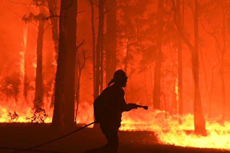 RFS volunteers and NSW Fire and Rescue officers protect a home southwest of Sydney on Tuesday. Source: AAP