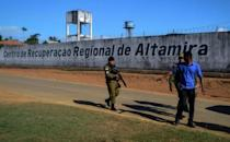 A police officer patrols the surroundings of the Altamira Regional Recovery Center after at least 57 inmates were killed during a prison riot, in the northern Brazilian city of Altamira, Para State