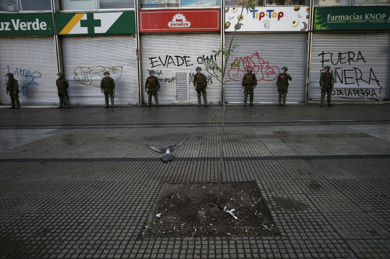 Police stand guard outside closed stores as a state of emergency remains in effect in Santiago, Chile, Sunday, Oct. 20, 2019. Protests in the country have spilled over into a new day, even after President Sebastian Pinera cancelled the subway fare hike that prompted massive and violent demonstrations. (AP Photo/Luis Hidalgo)