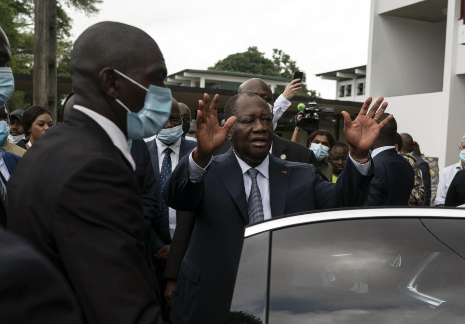 Ivory Coast President Alassane Ouattara waves to the people as he leaves a polling station after voting in the presidential elections in Abidjan, Ivory Coast, Saturday, Oct. 31, 2020. Tens of thousands of security forces deployed across Ivory Coast on Saturday as the leading opposition parties boycotted the election, calling President Ouattara's bid for a third term illegal. (AP Photo/Leo Correa)