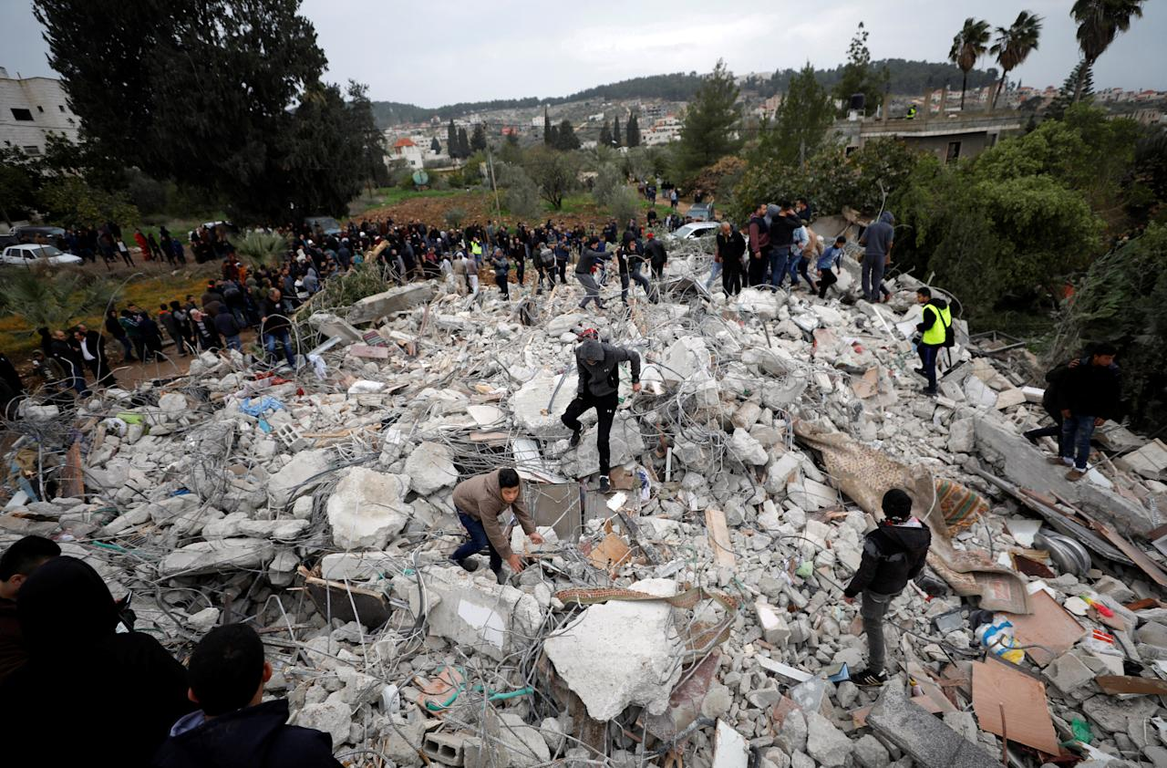 People stand on the rubble of the house of Palestinian gunman Ahmed Jarrar following an Israeli raid, in the West Bank city of Jenin, January 18, 2018. REUTERS/Mohamad Torokman