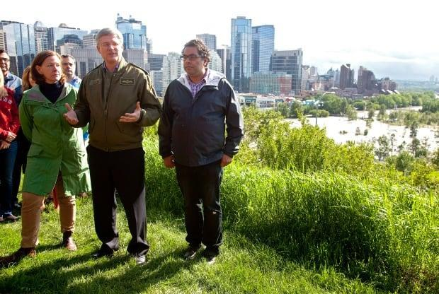 Former prime minister Stephen Harper, centre, with former Alberta premier Alison Redford, left, and Calgary Mayor Naheed Nenshi, speak to the media with the flooded Bow river behind them on June 21, 2013.
