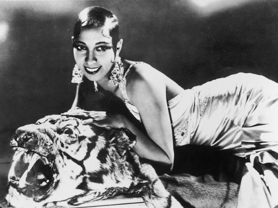 <p>Baker sweetly poses over a tiger rug dressed in a silk and jeweled evening gown and wearing her signature oversized statement earrings. </p>