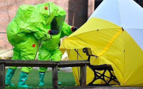 Members of the emergency services in green biohazard encapsulated suits afix a tent over the bench on which the Skripals were found - Credit: BEN STANSALL /AFP
