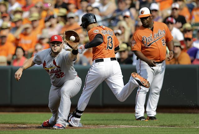 Baltimore Orioles' Manny Machado (13) narrowly beats a throw to St. Louis Cardinals first baseman Matt Adams as first base coach Wayne Kirby watches in the first inning of an interleague baseball game, Saturday, Aug. 9, 2014, in Baltimore. (AP Photo/Patrick Semansky)