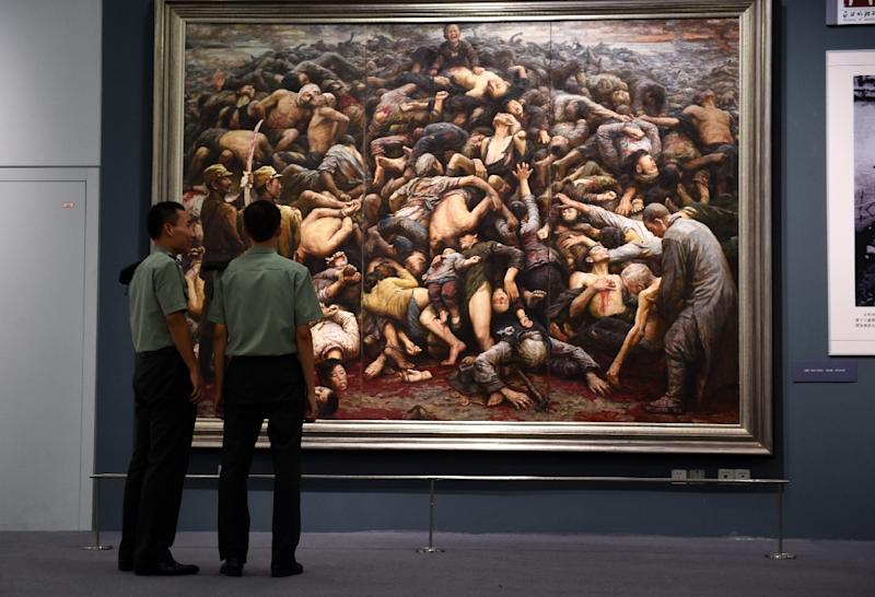 File picture shows Chinese soldiers looking at a painting depicting the Nanjing massacre, at an exhibition about World War II in Beijing (AFP Photo/Greg Baker)