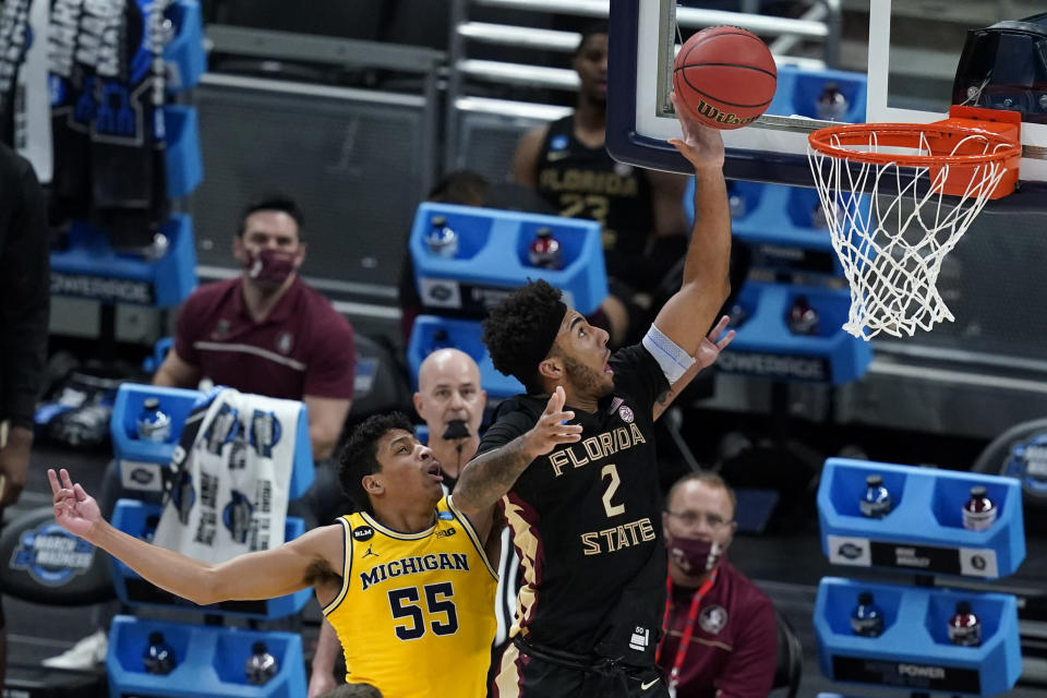 Florida State guard Anthony Polite shoots ahead of Michigan guard Eli Brooks (55) during the second half of a Sweet 16 game in the NCAA men's college basketball tournament at Bankers Life Fieldhouse, Sunday, March 28, 2021, in Indianapolis. (AP Photo/Darron Cummings)