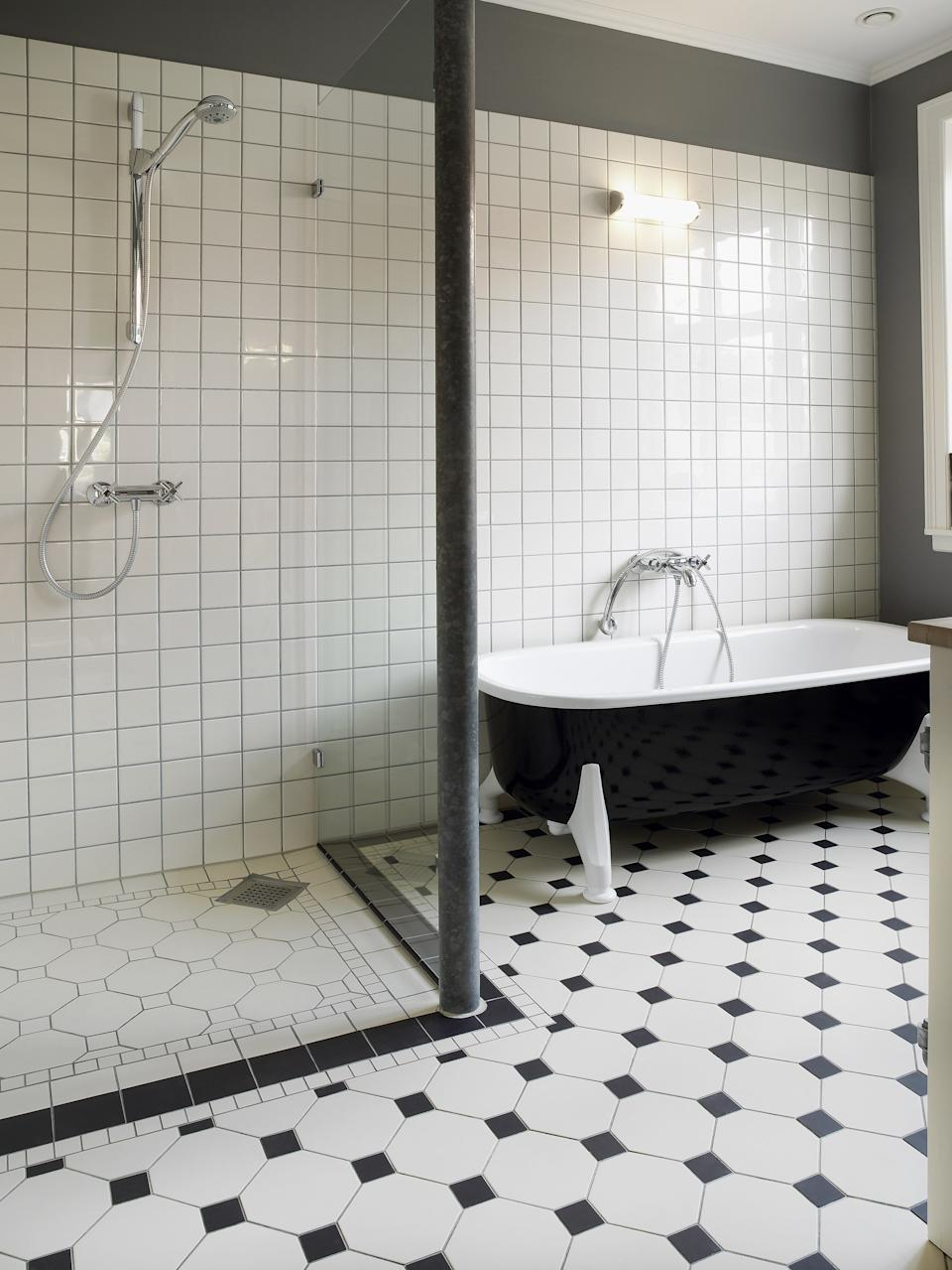 Totally renovated bathroom with shower cabin and bathtub,light cream coloured tiles on floor and wall. Point of focus mainly on tiles in forground.