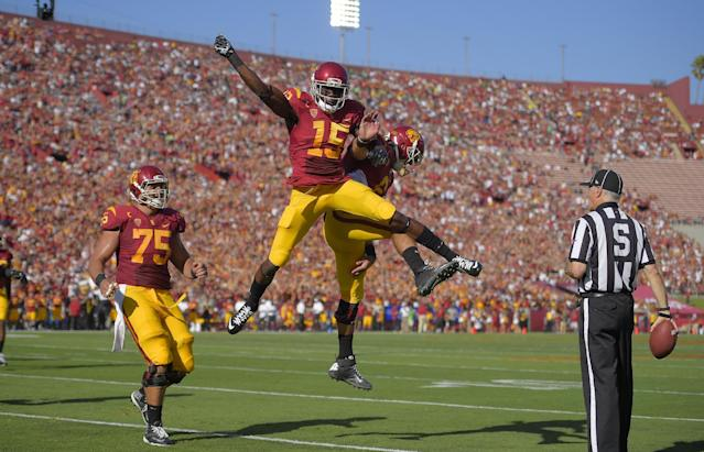 Southern California wide receiver Nelson Agholor, second from left, celebrates with quarterback Cody Kessler as center Max Tuerk, left, looks on after scoring a touchdown during they first half of an NCAA college football game against Fresno State, Saturday, Aug. 30, 2014, in Los Angeles. (AP Photo/Mark J. Terrill)
