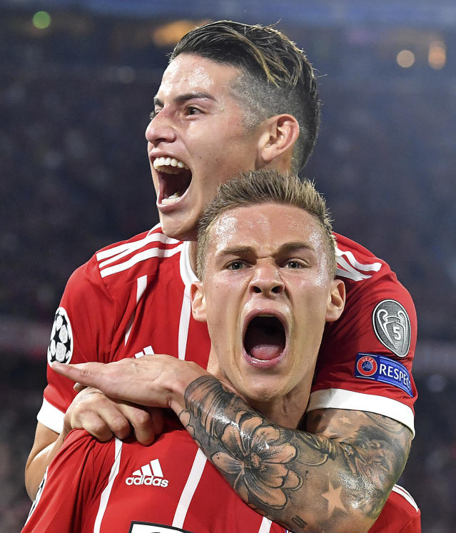 Bayern's Joshua Kimmich, bottom, celebrates his side's opening goal with team mate James during the semifinal first leg soccer match between FC Bayern Munich and Real Madrid at the Allianz Arena stadium in Munich, Germany, Wednesday, April 25, 2018. (AP Photo/Kerstin Joensson)