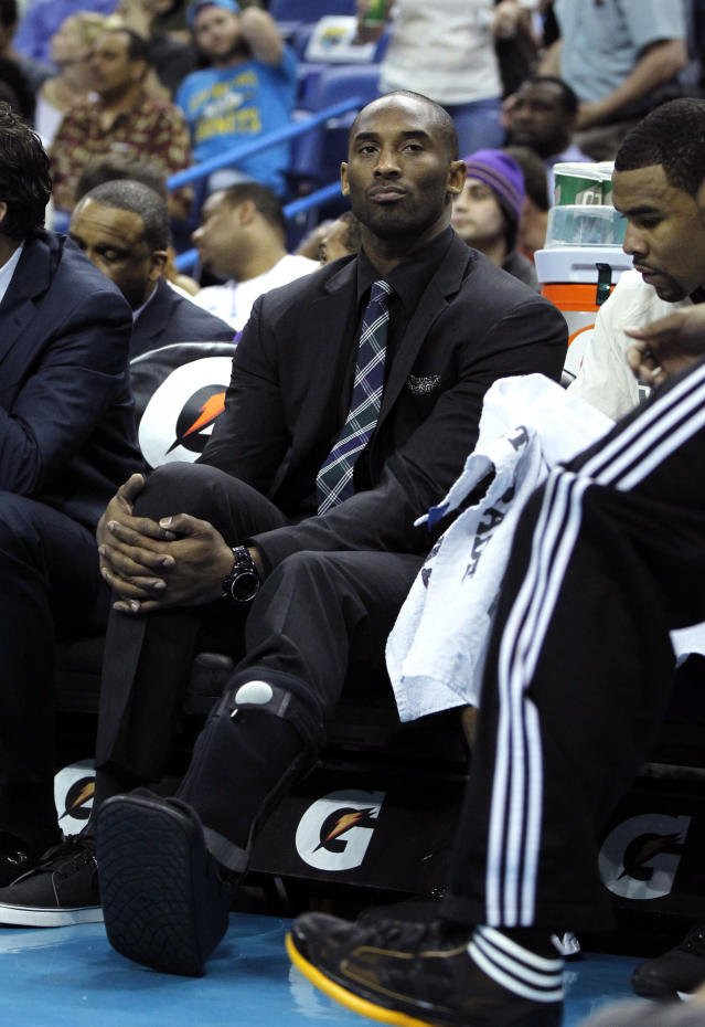 Los Angeles Lakers shooting guard Kobe Bryant watches from the bench with a cast on his foot in the first half of an NBA basketball game against the New Orleans Hornets in New Orleans, Monday, April 9, 2012. (AP Photo/Gerald Herbert)