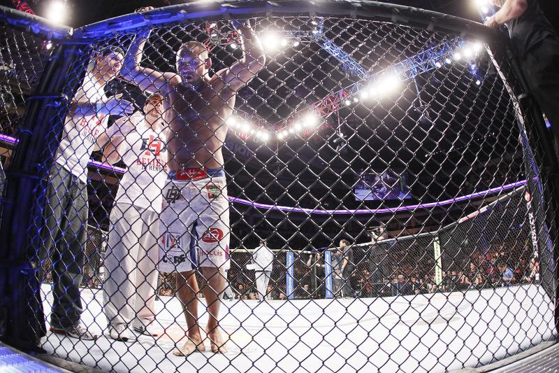 A dejected Dan Henderson hangs onto the net after his light heavyweight bout with Rashad Evans at UFC 161 in Winnipeg, Manitoba on Saturday June 15, 2013. (AP Photo/The Canadian Press, John Woods)