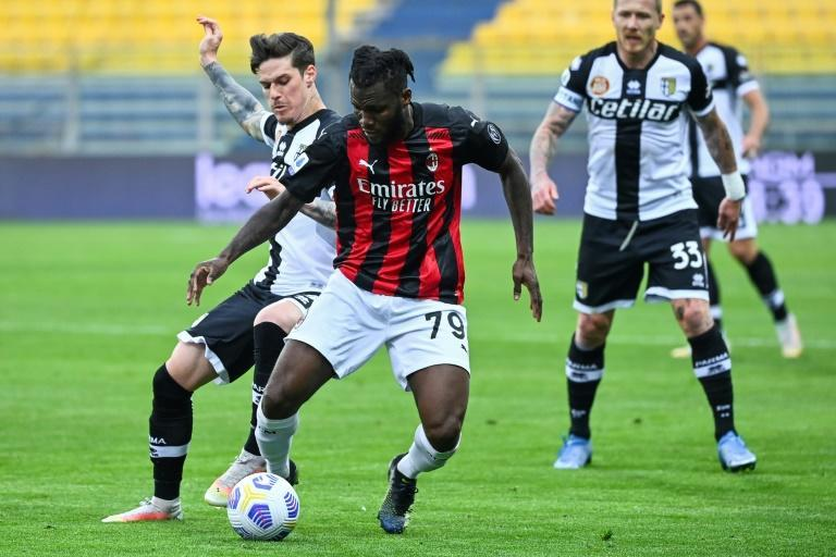 Franck Kessie (C) of AC Milan wins a tussle for possession against Parma