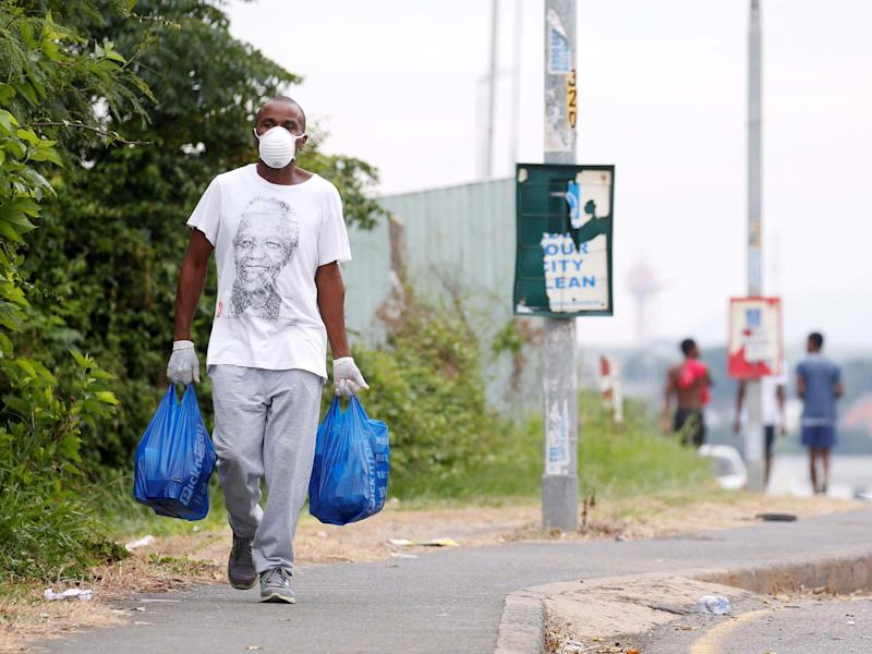 A man carries home groceries during a nationwide 21-day lockdown in an attempt to contain the coronavirus disease outbreak in Umlazi township near Durban, South Africa: Rogan Ward/Reuters