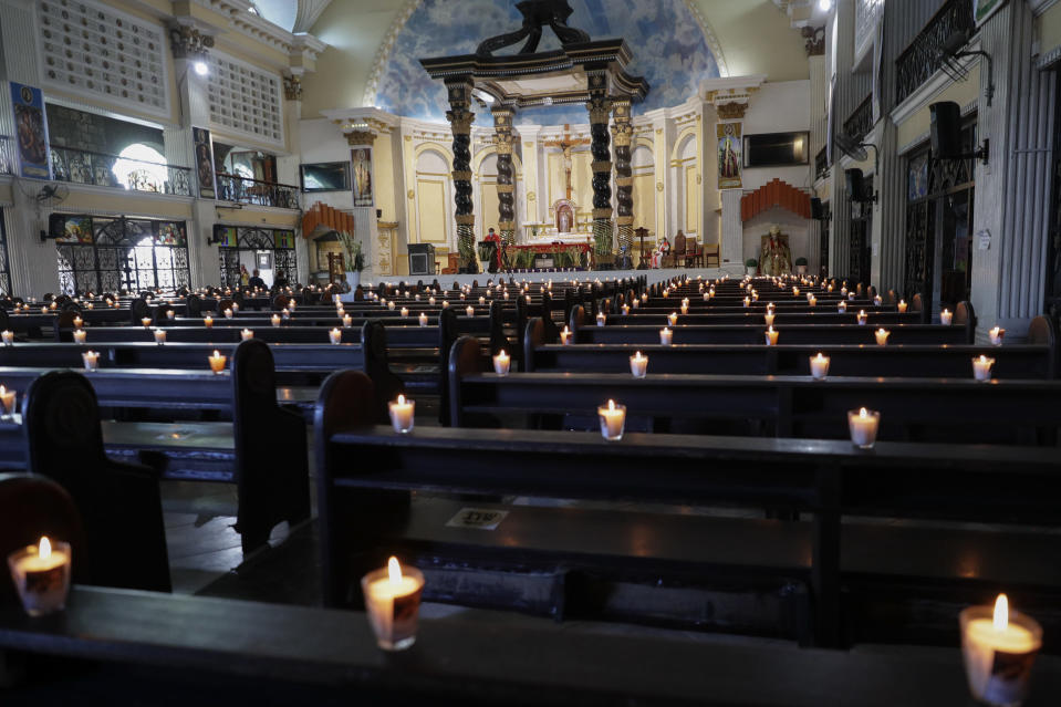 Lighted candles are placed on empty pews as Catholic priest presides over a Palm Sunday mass to prevent the spread of the coronavirus at the Saint Peter Parish Church in Quezon city, Philippines on March 28, 2021. The government banned religious activities during the Holy Week as it enters into stricter lockdown measures starting next week while the country struggles to control an alarming surge in COVID-19 cases. (AP Photo/Aaron Favila)