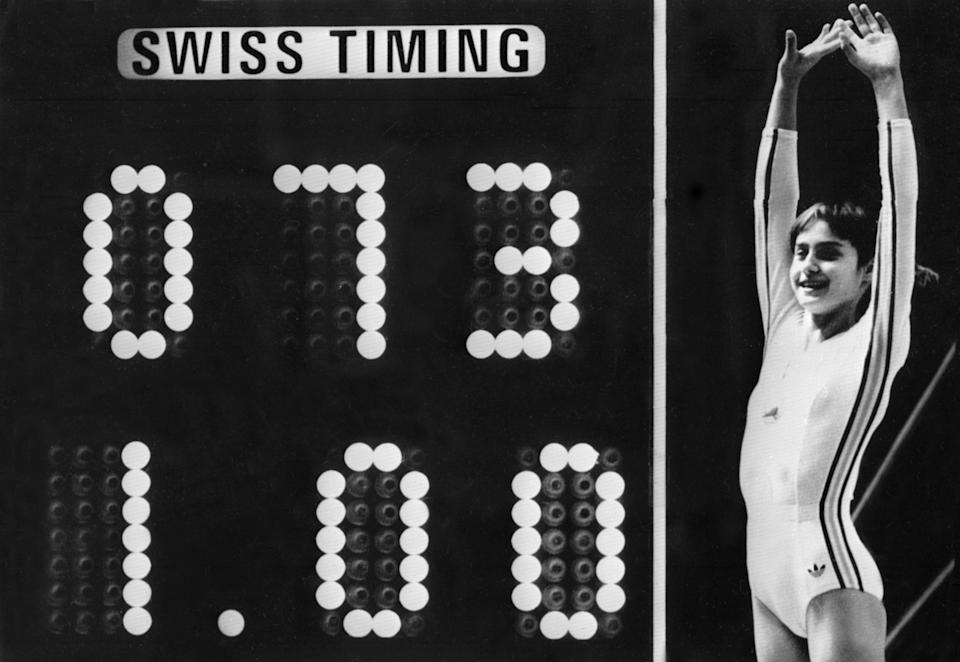 Rumanian champion Nadia Comaneci, aged 14, jubilates when scoreboard shows the perfect score of 10 during Olympic Games 19 July 1976 in Montreal after her acrobatic compulsory at uneven bars. She was awarded with ten points in two exercices and captured 3 gold medals (beam, uneven bars and general competition). Legendary gymnast, during her career Nadia Comaneci captured four Olympic gold medals (1976 : beam, uneven bars and general competition - 1980, beam) and was the first to score 10 in her discipline. / AFP PHOTO / -        (Photo credit should read -/AFP via Getty Images)