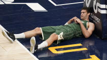Milwaukee Bucks center Brook Lopez falls while chasing a lthe ball in the second half during an NBA basketball game against the Milwaukee Bucks, Friday, Feb. 12, 2021, in Salt Lake City. (AP Photo/Rick Bowmer)