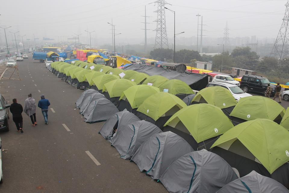 Indian farmers walk outside their tents on a blocked highway during a protest against the central government's recent agricultural reforms in Delhi, along the Delhi-Uttar Pradesh state border, on December 30, 2020. (Photo by Pankaj Nangia/Anadolu Agency via Getty Images)