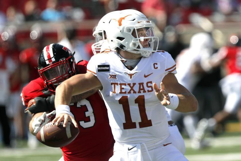 Texas quarterback Sam Ehlinger passes downfield under pressure from defensive lineman Eli Howard during the first half of an NCAA college football game against Texas Tech, Saturday Sept. 26, 2020, in Lubbock, Texas. (AP Photo/Mark Rogers)