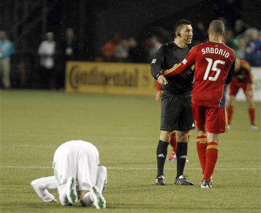 The referee admonishes Real Salt Lake forward Alvaro Saborio, right, for fouling Portland Trail Blazers defender Eric Brunner during the first half of their MLS soccer game in Portland, Ore., Saturday, March 31, 2012.(AP Photo/Don Ryan)