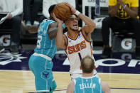 Phoenix Suns guard Devin Booker (1) drives past Charlotte Hornets guard Terry Rozier (3) during the second half of an NBA basketball game, Wednesday, Feb. 24, 2021, in Phoenix. (AP Photo/Matt York)