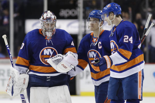 New York Islanders goaltender Semyon Varlamov, left, reacts with teammates Anders Lee, center, and Scott Mayfield, right, after an NHL hockey game against the Boston Bruins, Saturday, Jan. 11, 2020, in New York. (AP Photo/Frank Franklin II)