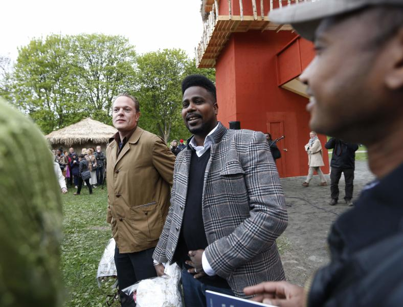 "Artists Lars Cuzner (L) and Mohamed Ali Fadlabi attend the opening of the ""Congo Village"" in Oslo May 15, 2014. The two artists hope their ""Congo Village"" display will help erase what they say is Norwegians' collective amnesia about racism. The Congo Village - which 100 years ago displayed African tribes, attracting 1.4 million visitors over four months - will this time exhibit volunteers taking turns living on show in makeshift huts, resembling a traditional sub-Saharan village. Picture taken May 15, 2014. REUTERS/Lise Aserud/NTB Scanpix (NORWAY - Tags: SOCIETY) ATTENTION EDITORS - THIS IMAGE HAS BEEN SUPPLIED BY A THIRD PARTY. FOR EDITORIAL USE ONLY. NOT FOR SALE FOR MARKETING OR ADVERTISING CAMPAIGNS. NORWAY OUT. NO COMMERCIAL OR EDITORIAL SALES IN NORWAY. THIS PICTURE IS DISTRIBUTED EXACTLY AS RECEIVED BY REUTERS, AS A SERVICE TO CLIENTS"