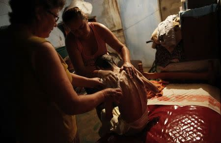 Cerebrovascular accident (CVA) patient Pedro, sits on his bed before being washed with the help of his daughter Daniela (R), 38, and wife Maria Do Carmo, 70, inside their house in Brasilandia slum, of which they are without water for 13 hours a day, in Sao Paulo February 11, 2015. REUTERS/Nacho Doce