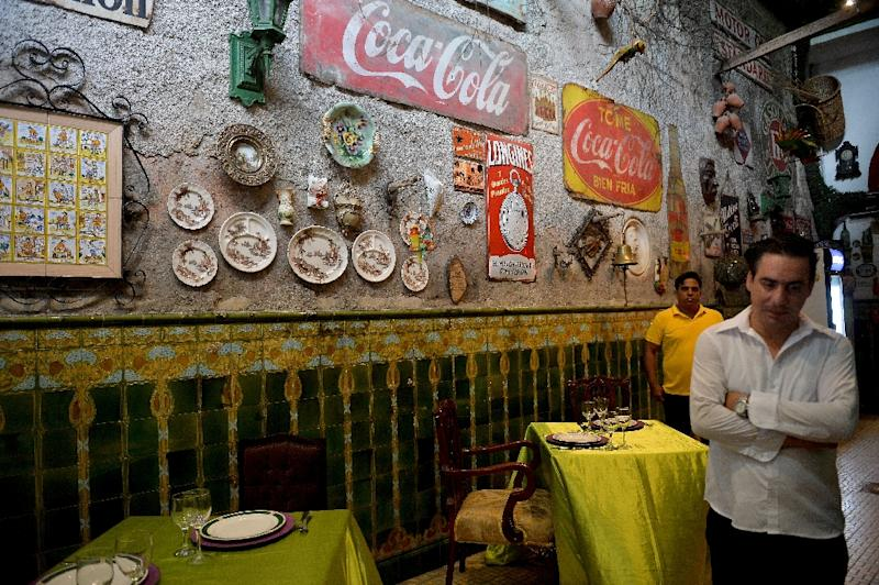 A waiter waits for clients at San Cristobal restaurant in Havana, enduring a slowdown blamed on new US sanctions (AFP Photo/YAMIL LAGE)