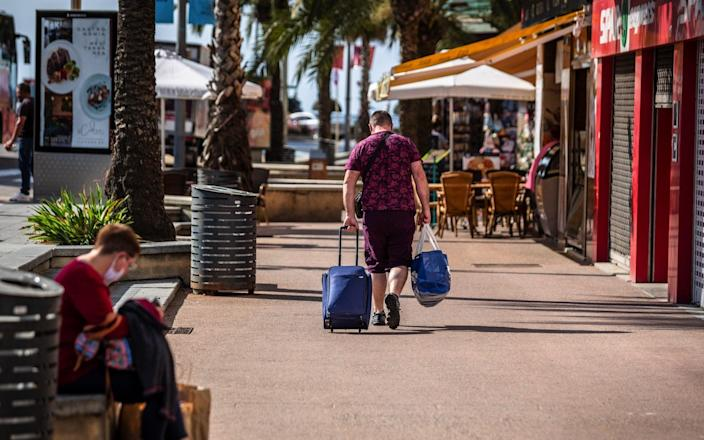 A tourist wheels luggage in Lloret de Mar, Spain - one of the countries that does not currently have a quarantine requirement for British travellers. - Angel Garcia/Bloomberg