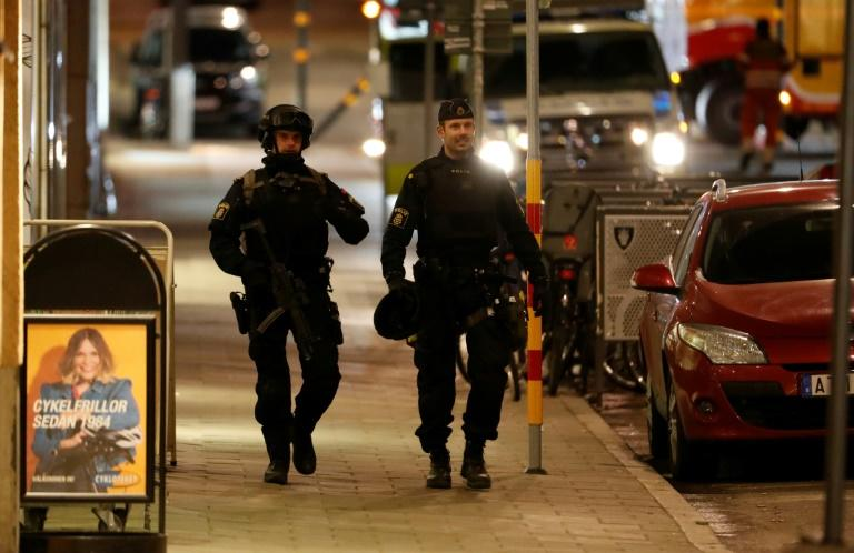 Swedish police officers patrol after a beer truck ploughed into a crowd outside a busy department store in central Stockholm, killing four and injuring 15