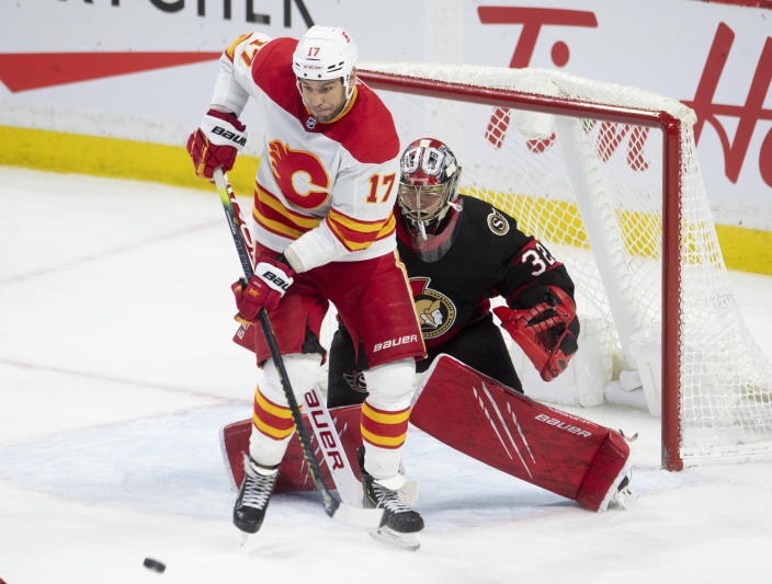 Calgary Flames left wing Milan Lucic screens Ottawa Senators goaltender Filip Gustavsson on a shot during the second period of an NHL hockey game Wednesday, March 24, 2021, in Ottawa, Ontario. (Adrian Wyld/The Canadian Press via AP)
