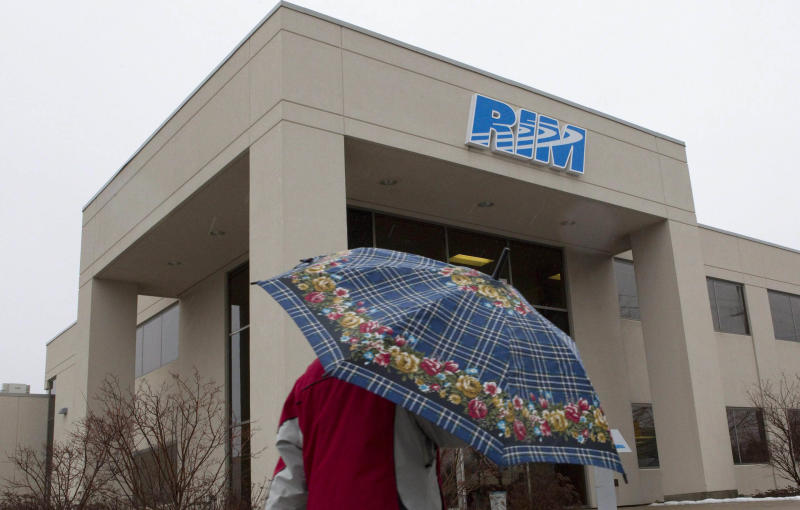 In this Monday, Jan. 23, 2012 photo, a man with an umbrella walks past part of the Research In Motion campus in Waterloo, Ontario, Canada. These are troubling times for Waterloo, the town of 100,000 that was transformed by Research In Motion's BlackBerry into Canada's Silicon Valley. (AP Photo/The Canadian Press, Chris Young)